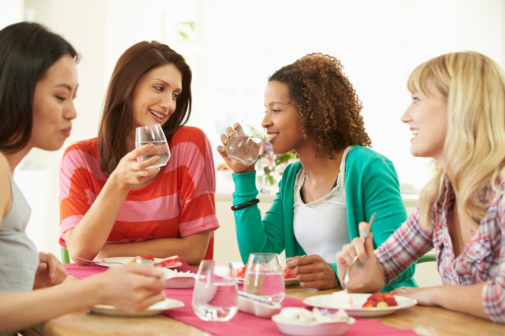 Group Of Women Sitting Around Table Eating Dessert